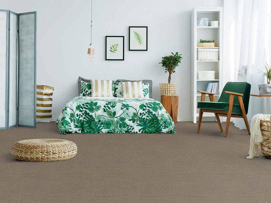 Bedroom with floor plant and leaf themed bedspread and painting