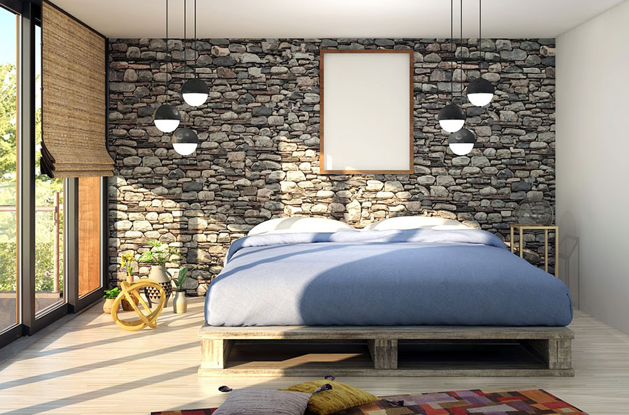 Bedroom with pallet style bed frame and stone wall